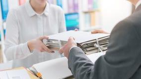 Boss handing paperwork to his employee stock photo