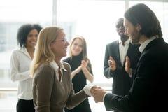Boss handshaking rewarding female employee congratulating with p