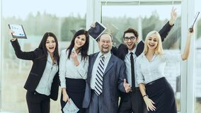 Boss and happy business team rejoice after signing a lucrative financial contract. Leader and successful business team cheering after signing a lucrative Stock Photo