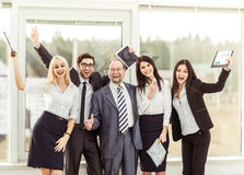 Boss and happy business team rejoice after signing a lucrative financial contract. Leader and successful business team cheering after signing a lucrative Royalty Free Stock Photography