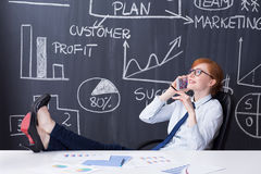 She is a boss here. Woman boss sitting with legs on a desk, talking on cellphone, business plan drawn on a blackboard in the background Royalty Free Stock Images