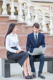 Boss and his assistant discussing their work outdoors. Boss in blue suit and his assistant in white blouse and black skirt discussing their work outdoors Royalty Free Stock Images