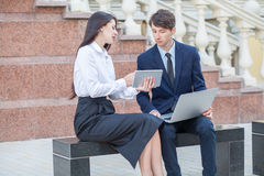 Boss and his assistant discussing their work outdoors. Boss in blue suit and his assistant in white blouse and black skirt discussing their work outdoors Royalty Free Stock Photography