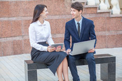Boss and his assistant discussing their work outdoors. Boss in blue suit and his assistant in white blouse and black skirt discussing their work outdoors Royalty Free Stock Photos
