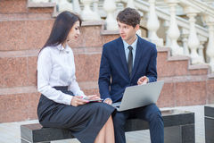 Boss and his assistant discussing their work outdoors. Stock Image