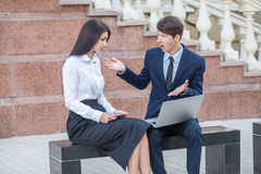 Boss and his assistant discussing their work outdoors. Royalty Free Stock Image