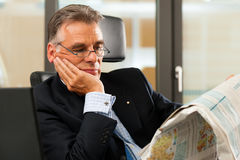 Boss in his office reading newspaper Royalty Free Stock Photo