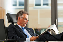 Boss in his office reading newspaper Stock Photo