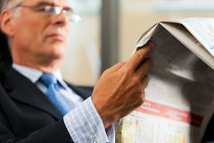 Boss in his office reading newspaper Royalty Free Stock Image