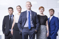 Boss and his team. Group of happy and young businesspeople posing in a light office interior Stock Images