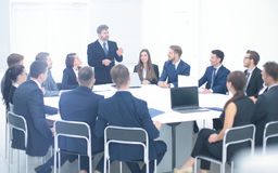 Boss holding company holds a working meeting with the heads of d. Heads of departments of the holding company at a meeting sitting at a round table and listening Royalty Free Stock Photos