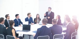 Boss holding company holds a working meeting with the heads of d. Heads of departments of the holding company at a meeting sitting at a round table and listening Royalty Free Stock Photography