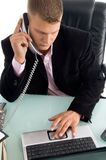 Boss holding the phone receiver and working. On laptop in an office Royalty Free Stock Photos
