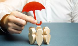 Boss holding a red umbrella and defending his team with a gesture of protection. Life insurance. Customer care, care for employees. Security and safety in a royalty free stock photography
