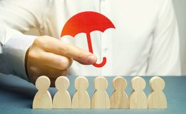 Boss holding a red umbrella and defending his team with a gesture of protection. Life insurance. Customer care, care for employees. Security and safety in a stock photos