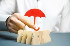 Boss holding a red umbrella and defending his team with a gesture of protection. Life insurance. Customer care, care for employees. Security and safety in a royalty free stock photo