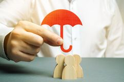 Boss holding a red umbrella and defending his team with a gesture of protection. Life insurance. Customer care, care for employees. Security and safety in a stock image