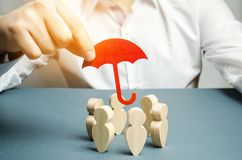 Boss holding a red umbrella and defending his team with a gesture of protection. Life insurance. Customer care, care for employees royalty free stock images
