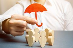 Boss holding a red umbrella and defending his team with a gesture of protection. Life insurance. Customer care, care for employees. Security and safety in a stock photo