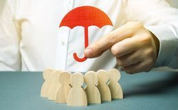 Boss holding a red umbrella and defending his team with a gesture of protection. Life insurance. Customer care, care for employees royalty free stock photo
