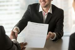 Recruiter giving employment agreement to applicant. Boss or human resources manager handshaking with male job candidate, offering employment agreement document Royalty Free Stock Photo