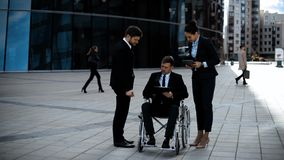 Boss in invalid wheelchair and his employe businesswoman with IPad sign documents stock video footage
