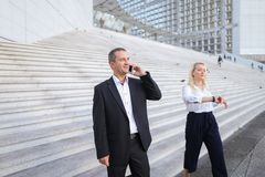 Secretary talking with boss keeping tablet on stairs with employ. Boss keeping tablet and speaking with blonde secretary on stairs with biz partners in Stock Photos