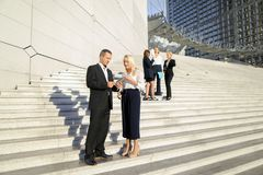 Secretary talking with boss keeping tablet on stairs with employ. Boss keeping tablet and speaking with blonde secretary on stairs with biz partners in Stock Photo