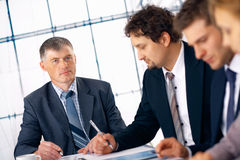 Boss Listens. Confident mature business man with his staff working at the office Royalty Free Stock Images