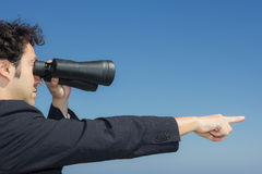 Boss looking at the horizon with binoculars and  his finger indi Royalty Free Stock Images