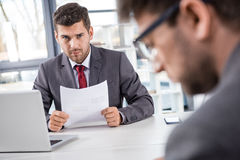 Boss looking at upset colleague at business meeting. Unsatisfied boss looking at upset colleague at business meeting Royalty Free Stock Photos