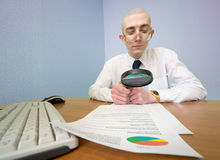 Boss with a magnifier on a workplace Stock Images