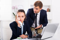 Boss man accusing crying woman to making mistake Stock Photo