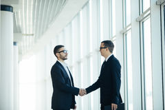 Boss and manager agree handshake. In office panoramic room Royalty Free Stock Photo