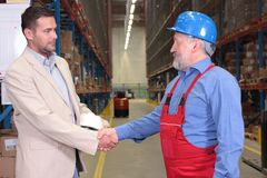 Boss + older worker handshake  Stock Photo
