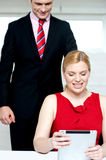 Boss operating tablet pc and assistant looking Stock Photos