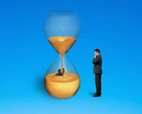 Boss oversee employee flooded in hourglass Stock Photo