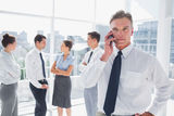 Boss on the phone standing in a modern office Stock Images