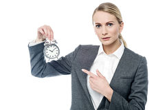 Boss pointing at alarm clock, you are late! Royalty Free Stock Photo
