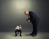 Boss que grita en el pequeño trabajador perezoso Imagen de archivo