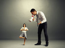 Boss que grita en la pequeña mujer tranquila Foto de archivo