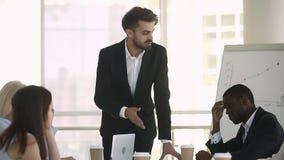 Boss que habla con los miembros de compañía diversos durante el encuentro en la sala de reunión almacen de metraje de vídeo