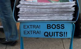Boss Quits headlined on Newspaper stack. Boss Quits Newspaper stack - take one of these newspaper in the subway entrance Stock Photo