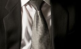 The boss`s tie. The businessman is wearing his dark grey jacket on the white shirt with an elegant grey tie stock image