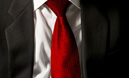 The boss`s tie. The businessman is wearing his dark gray jacket on the white shirt with a gaudy red tie royalty free stock image