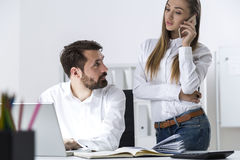 Boss and a secretary on her phone Royalty Free Stock Images