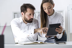 Boss and secretary looking at calculator Royalty Free Stock Photography