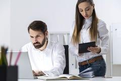Boss and secretary looking at talbet Stock Photo