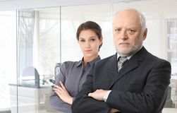 Boss and secretary. Portrait of senior male boss and young female secretary standing arms crossed Royalty Free Stock Photo