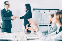 boss shaking hand of asian manageress at conference hall while stock photography
